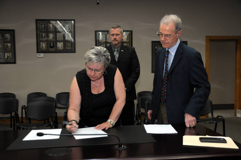 Bargaining member Anna Joseph signs the new five year deal for Cornwall Police Association members Friday, May 13, 2016 at Cornwall city hall. CPA President Dave MacLean, background, and police board member Pat Finucan look on. (Newswatch Group/Bill Kingston)