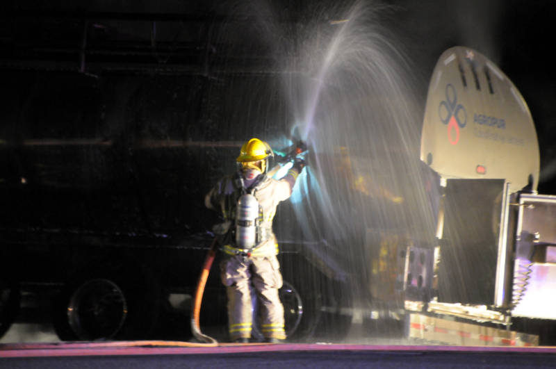 A Cornwall firefighter sprays water inside the stainless steel tank after puncturing holes in it to release any pressure. The trailer was labelled AgroPur, a Quebec dairy cooperative. (Newswatch Group/Bill Kingston)