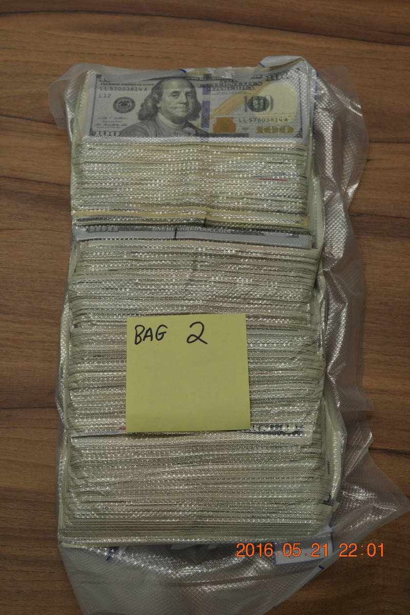 In this Monday, June 6, 2016 photo provided by the Canada Border Services Agency, an evidence photo shows one of the 13 bags seized by border agents on May 21, 2016 at Cornwall's port of entry. Officers found $129,000 in American cash. (CBSA via Newswatch Group)