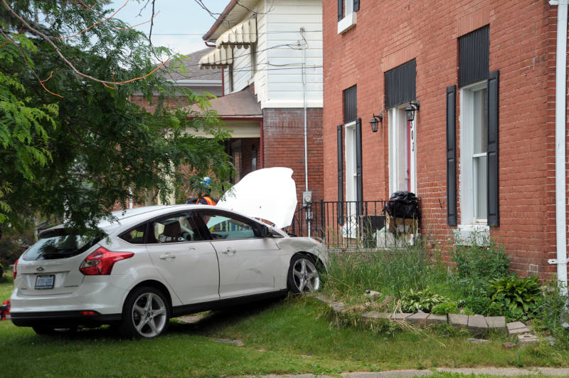 A Ford Focus hatchback rests up against a set of concrete stairs Wednesday, June 28, 2016 after a two vehicle crash at the intersection of Second and Bedford Streets in Cornwall, Ont. One woman was taken to hospital as a precaution. (Newswatch Group/Bill Kingston)