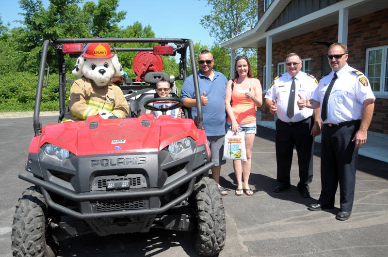 Lhandon Heagle-Francis (seated on the ATV with Sparky) is recognized for spotting a fire on County Road 2 in May that likely saved the home from serious damage. Pictured are Sparky, Lhandon Heagle-Francis, father Justin Francis, mom Khrista Heagle-Francis, South Glengarry Deputy Chief Gabriel McEvoy and Assistant Deputy Chief Brian Poirier. (Newswatch Group/Bill Kingston)