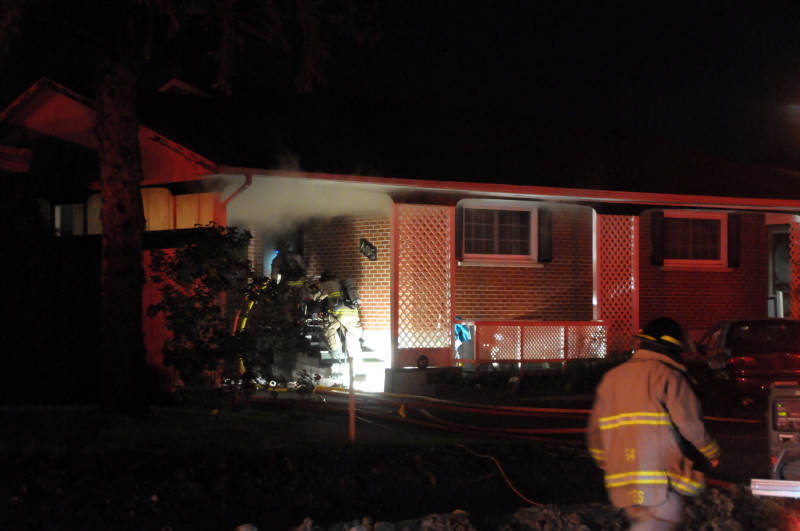 Two Cornwall firefighters get ready to head in and battle a fire Tuesday, July 12, 2016 at a home on Anderson Drive in Cornwall, Ont. The fire caused extensive damage to the basement and main floors. (Newswatch Group/Bill Kingston)