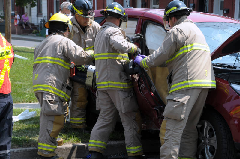 Four Cornwall firefighters use the Jaws of Life to pry the doors off an Hyundai Tuscon to free a woman trapped in the passenger seat. The SUV was involved in a collision with a Cornwall Transit bus Wednesday, July 20, 2016 at the intersection of First and York Streets. (Newswatch Group/Bill Kingston)