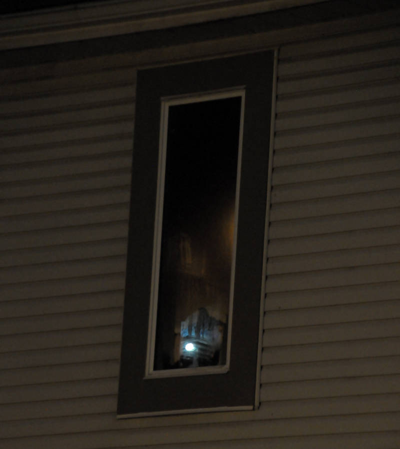 A Cornwall firefighter's flashlight reflects off a soot-covered bedroom window Monday, July 18, 2016 after a fire in a child's closet at a townhouse on Lemay Street in Cornwall, Ont. Two people in the unit were able to escape uninjured. (Newswatch Group/Bill Kingston)
