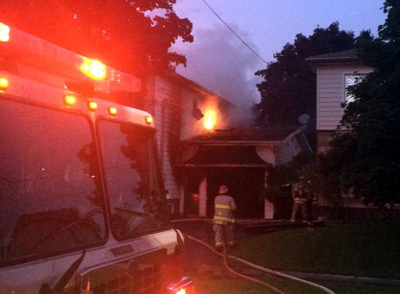 In this Wednesday, Aug. 31, 2016 photo supplied by Keelan O'Flaherty, flames leap from a section of the roof next to the garage of this two storey home on Gardner Avenue. (Keelan O'Flaherty via Newswatch Group)