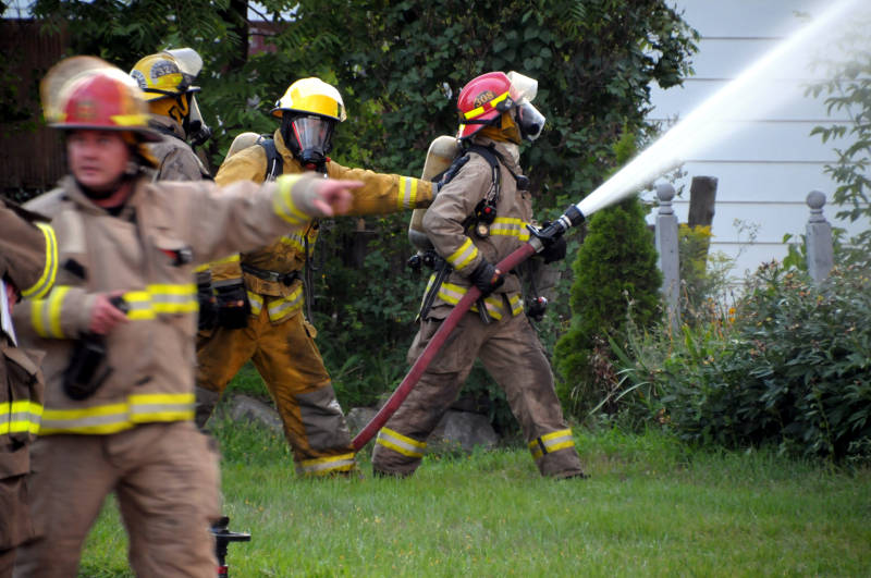 A South Stormont firefighter braces a colleague Thursday, Aug. 18, 2016 as they battle a house fire in the village of Newington. The home, on the curve of County Road 12/14 in the village is a total loss. (Newswatch Group/Bill Kingston)