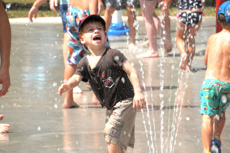 Byron Rohde, 3, runs away from a sprinkler at the splash pad in Riverdale Park, shortly after its opening Friday, Aug. 5, 2016. (Newswatch Group/Bill Kingston)