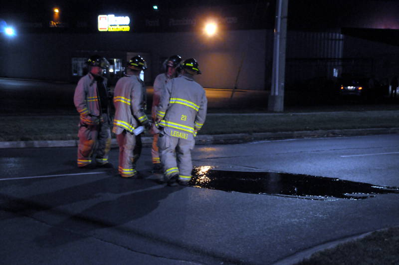 Cornwall firefighters use a solvent and water to wash down blood on Pitt Street on Wednesday, Sept. 28, 2016 after a collision between a cyclist and a car. (Newswatch Group/Bill Kingston)