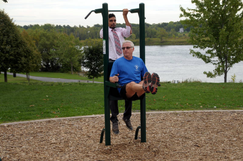 Rotarians Sebastian Warner and Pat Clarke demonstrate a piece of equipment at the Rotary Outdoor Gym on Thursday, Sept. 22, 2016 during the official handover of the Lamoureux Park workout facility to the City of Cornwall. The rotary clubs still need to raise around $20,000 through sponsorships to cover the project. (Newswatch Group/Bill Kingston)