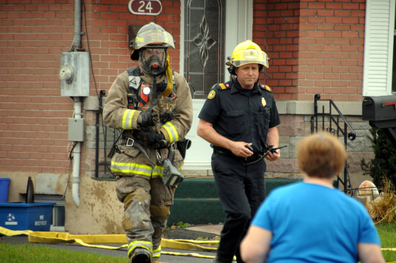 Cornwall firefighter Alex Monpetit reunites one of two cats with the homeowner, foreground, rescued from a Crescent View Drive home on Thursday, Nov. 17, 2016. Also with Monpetit is Acting Platoon Chief Jody Dewar. The fire is believed to have started in a pot left on the stove. (Newswatch Group/Bill Kingston)