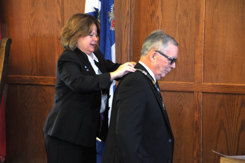 South Stormont Deputy Mayor Tammy Hart attaches the chain of office on Warden Jim Bancroft during a ceremony at the United Counties building on Friday, Dec. 16, 2016. This is not the first time Bancroft has been warden after holding the post two decades ago. (Newswatch Group/Bill Kingston)